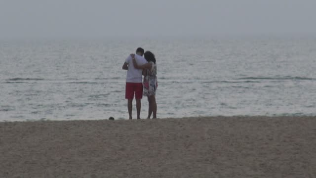 Indian tourists On hazy day with motorboat passing across screen At Mobar Goa