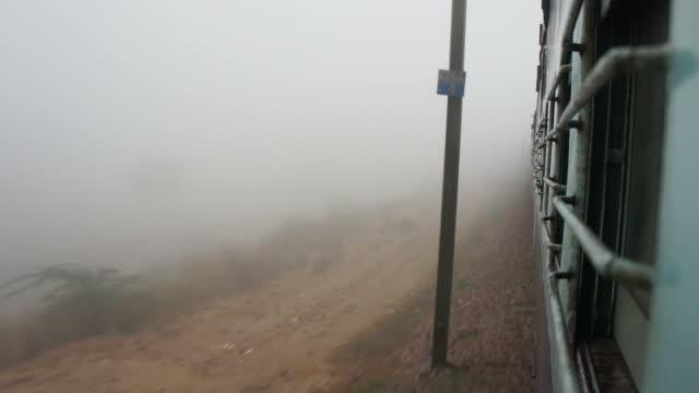 indische eisenbahn reiten bis foggy landschaft - railway track stock-videos und b-roll-filmmaterial