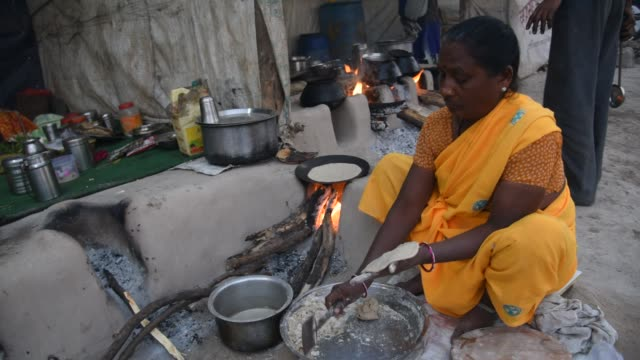 indian woman cooking food vintage kitchen using firewood. - rice stock videos & royalty-free footage
