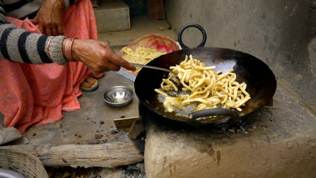 Indian woman cooks traditional snacks on adobe stove.