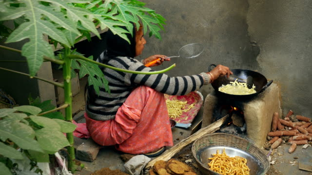 indian woman cooks traditional snacks on adobe stove. - indian food stock videos & royalty-free footage