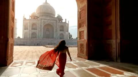 vídeos y material grabado en eventos de stock de mujer india en saree/sari rojo en el taj mahal, agra, uttar pradesh, india - culturas