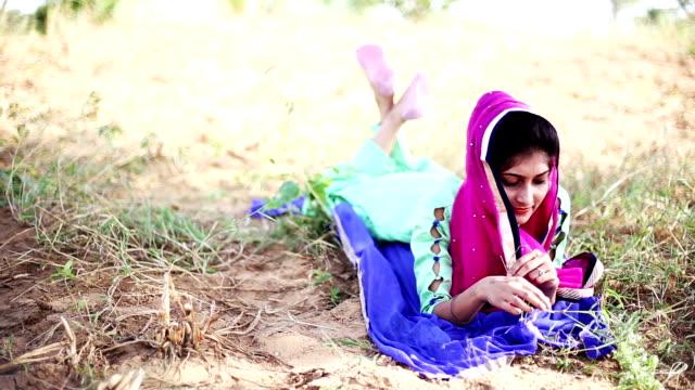 vidéos et rushes de femme indienne fixant et assurant la correspondance avec l'herbe - assis en tailleur
