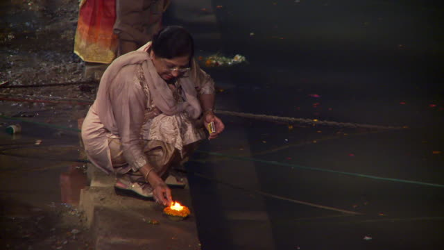 Indian woman lighting relighting a floating candle.