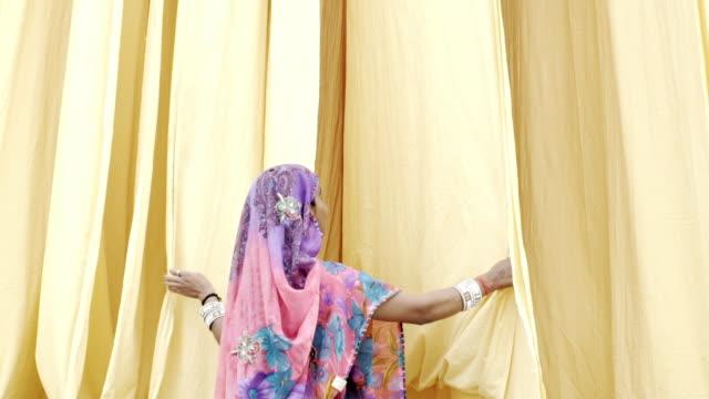 indian woman wearing sari, looking at hanging fabric. jaipur. india. - sari stock videos & royalty-free footage