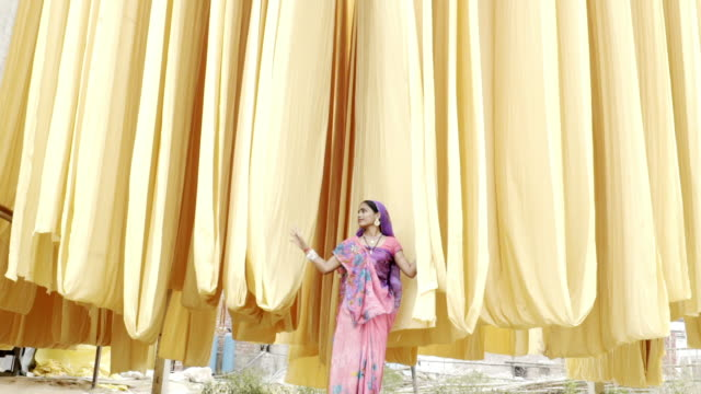 Indian woman wearing sari, looking at hanging fabric. Jaipur. India.