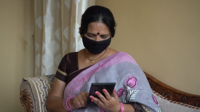 indian woman with face protective mask reading news on tablet. - portable information device stock videos & royalty-free footage