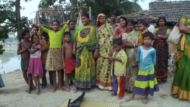 Indian women and children posing for the camera.