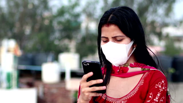 indian women covering her face with pollution mask for protection against covid-19 and using mobile phone - handheld stock videos & royalty-free footage