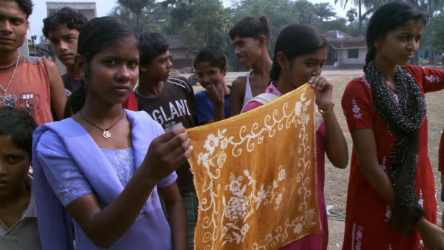 Indian women showing embroidered shawls.