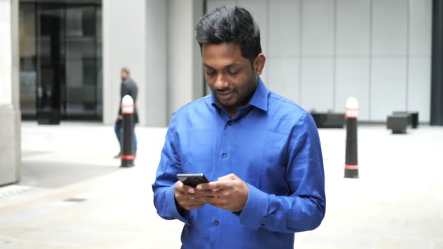 indian young businessman in london, using the phone outdoors - hinduism stock videos & royalty-free footage