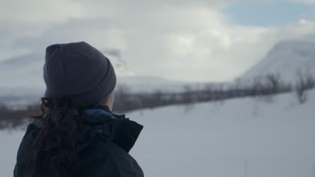 indisk ung kvinna som står framför lapplands port i ett snöigt vinterlandskap med vinterkläder - ourbaniserat motiv bildbanksvideor och videomaterial från bakom kulisserna