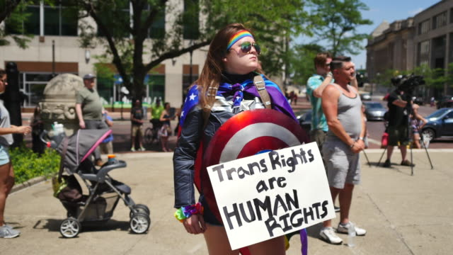 a person dressed as a superhero carries a sign reading trans rights are human rights members of the lgbtq community and their allies gather to rally... - societal symbol stock videos & royalty-free footage