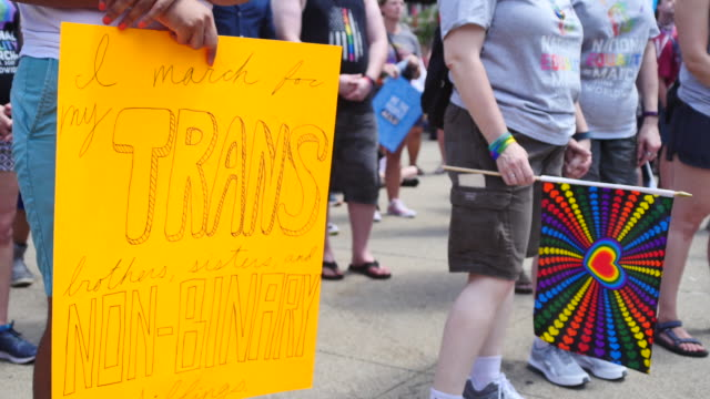vidéos et rushes de a person holds a sign referring to trans rights members of the lgbtq community and their allies gather to rally at monument circle in solidarity with... - trans