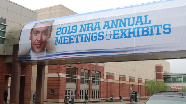 indianapolis, indiana, usa: a photograph of nra-ila executive director chris w. cox is emblazoned on a banner outside the indiana convention center... - 全米ライフル協会点の映像素材/bロール