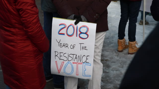 A protester holds a sign reading 2018 Year of the Resistance Vote during the 2018 Women's March on the first anniversary of Donald Trump's presidency...