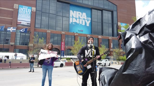 """indianapolis, indiana, usa: a protester sings, """"fuck you donald trump, indy hates you,"""" as protesters demonstrate outside lucas oil stadium while... - 全米ライフル協会点の映像素材/bロール"""