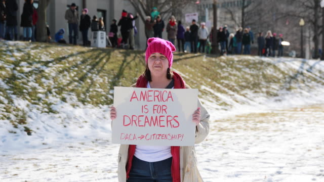 A woman holds a sign in support of DACA before the Women's March to the Indiana Statehouse on the first anniversary of Donald Trump's presidency...