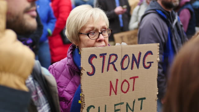stockvideo's en b-roll-footage met a woman in her 70s holds a sign reading strong not silent in my 70s during the 2018 women's march on the first anniversary of donald trump's... - 70 79 jaar