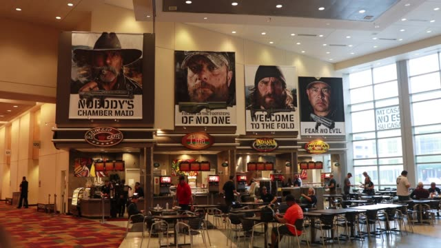 Advertising posters dominate the view inside a cafe before the National Rifle Association convention at the Indiana Convention Center in downtown...