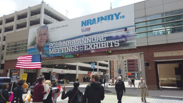 an image of nra president oliver north is emblazoned on a banner outside the indiana convention center as protesters march past during the national... - national rifle association stock videos & royalty-free footage