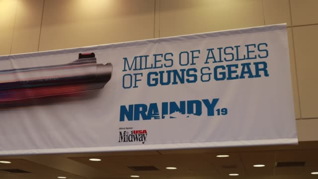 An NRA banner is affixed to a wall as vendors prepare booths in an exhibition hall before the National Rifle Association convention at the Indiana...