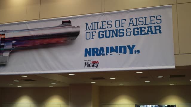 indianapolis, indiana, usa: an nra banner is affixed to a wall as vendors prepare booths in an exhibition hall before the national rifle association... - 全米ライフル協会点の映像素材/bロール