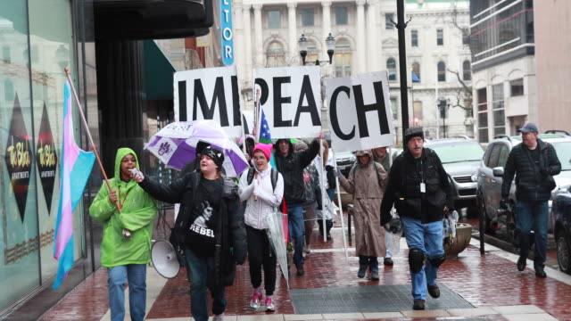 protesters carry signs that spell the word impeach while marching during a the hoosiers march on indianapolis the impeachment march january 27 2018... - marching stock videos & royalty-free footage
