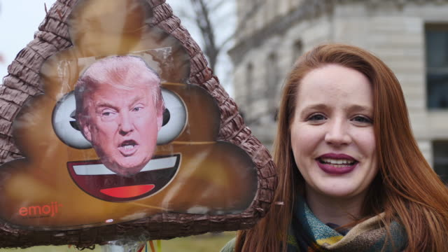 Shannon Paige Christie talks about United States President Donald J Trump's 'shithole countries' comment while holding a turd emoji she made as a...