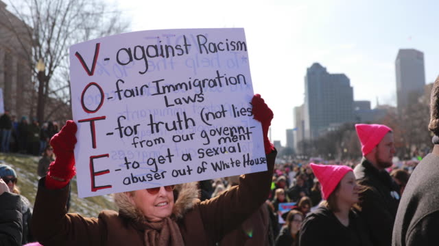 WA marcher holds a sign reading VOTE against racism fair immigration laws for truth not lies from the government and to get a sexual abuser out of...