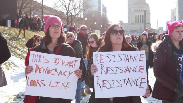 Women hold signs during the 2018 Women's March in Indianapolis Indiana on the first anniversary of Donald Trump's presidency Saturday January 18 2018...