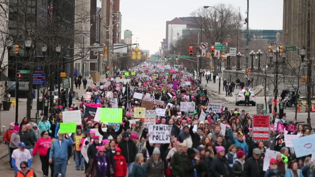 women's march participants fill north meridian street while marching to the indiana statehouse on the first anniversary of donald trump's presidency... - marching stock videos & royalty-free footage