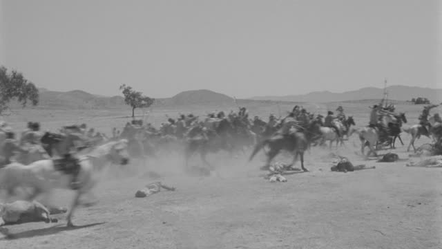 ws pan indians riding fast across plains past dead soldiers and horses on ground - north american tribal culture stock videos and b-roll footage
