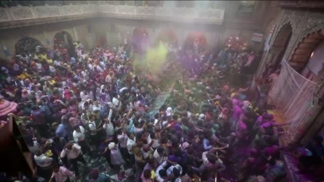 vídeos y material grabado en eventos de stock de indians smeared with coloured powder take part in the holi festival celebrations at banke bihari temple in vrindavan india on march 19 2016 holi the... - vrindavan