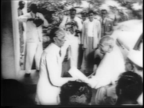 stockvideo's en b-roll-footage met india's muslim leader, muhammad ali jinnah, meets for discussions with mahatma gandhi at his palatial home / reporters wait outside / gandhi makes... - mahatma gandhi