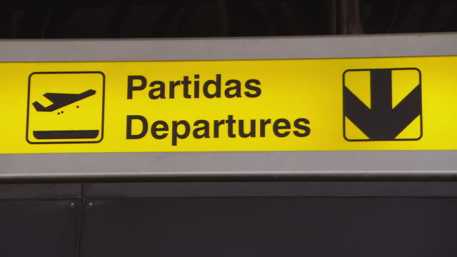"vidéos et rushes de ms pan indication signals ""departures"" and ""terminal 1"" at airport / lisbon, portugal   - montrer la voie"