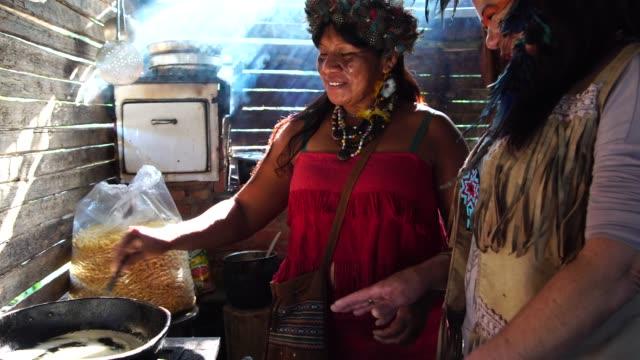 """vídeos de stock, filmes e b-roll de mulheres indígenas brasileiras, de etnia guarani, cozinhar """"xipa"""" - aldeia"""
