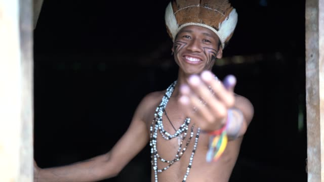 indigenous brazilian young man beckoning and welcoming tourists - from guarani ethnicity - sustainable tourism stock videos & royalty-free footage