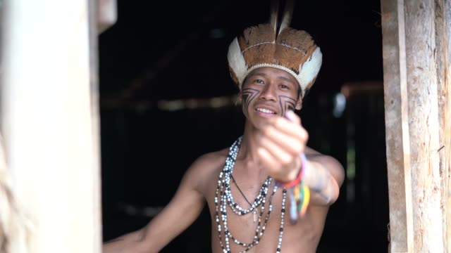 vídeos de stock e filmes b-roll de indigenous brazilian young man beckoning and welcoming tourists - from guarani ethnicity - cultura indígena