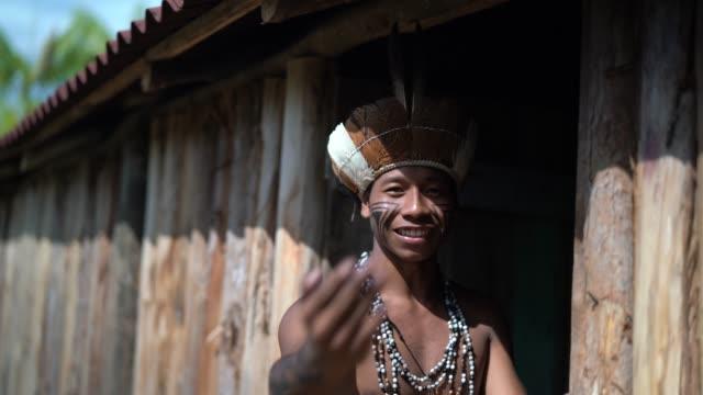 einheimischen brasilianischen jungen mann winkte und einladende touristen - von guarani ethnizität - heranlocken stock-videos und b-roll-filmmaterial