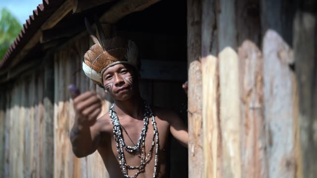 Indigenous Brazilian Young Man Beckoning and Welcoming Tourists - from Guarani ethnicity