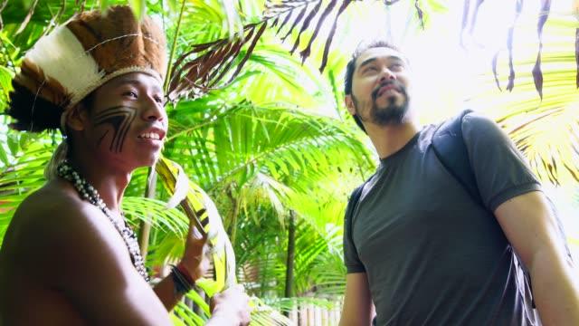 stockvideo's en b-roll-footage met inheemse braziliaanse jonge man uit guarani etniciteit tonen het regenwoud aan toeristische - inheemse cultuur