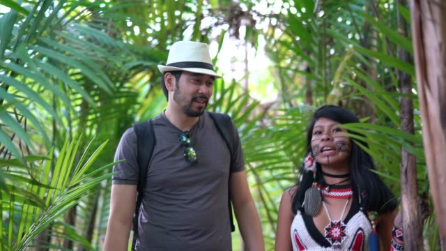 indigenous brazilian young woman from guarani ethnicity showing the rainforest to tourist - guidance stock videos & royalty-free footage