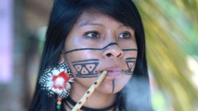vídeos de stock, filmes e b-roll de cachimbo de mulher jovem brasileira indígena, da etnia guarani - índio americano