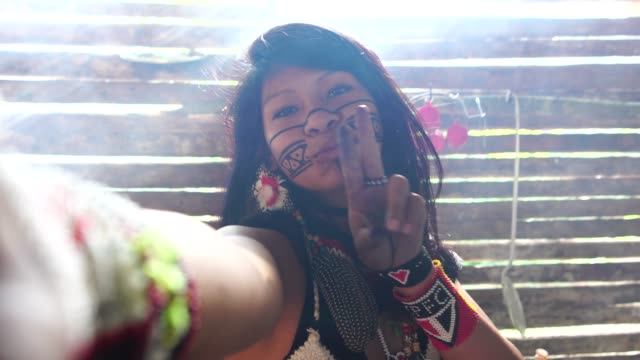 vídeos de stock e filmes b-roll de indigenous brazilian young woman taking a selfie, from tupi guarani ethnicity, in a hut - cultura tribal da américa do norte