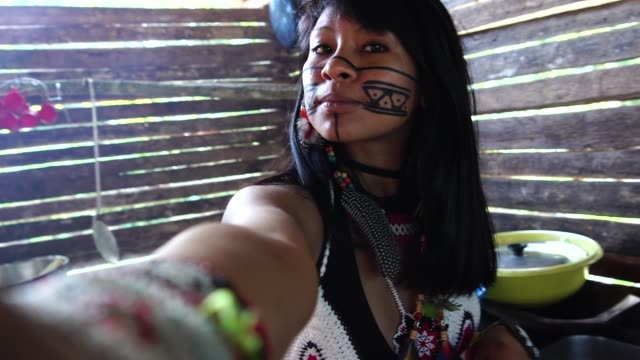 vídeos de stock e filmes b-roll de indigenous brazilian young woman taking a selfie, from tupi guarani ethnicity, in a hut - índio americano