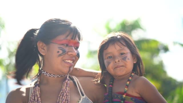 ブラジルの先住民族の若い女性と彼女の子供は、トゥピ族グアラニー語民族性からの肖像画 - 式典点の映像素材/bロール