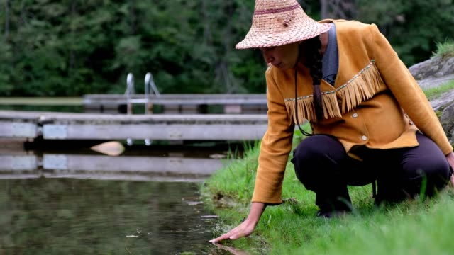 indigenous canadian woman blessing the water - traditionally canadian stock videos & royalty-free footage