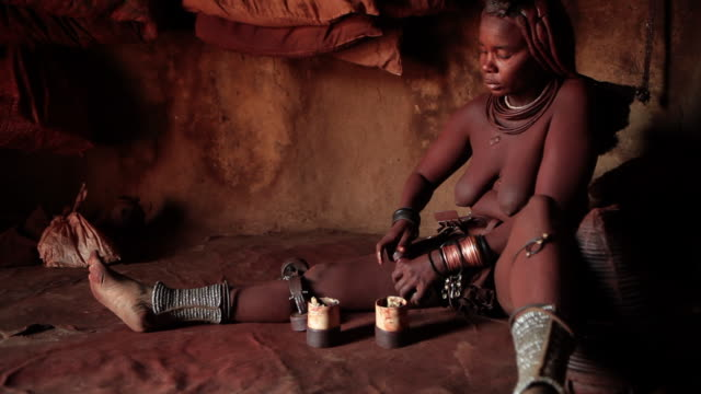 indigenous himba women from namibia doing her cleaning ritual. - fußkettchen stock-videos und b-roll-filmmaterial