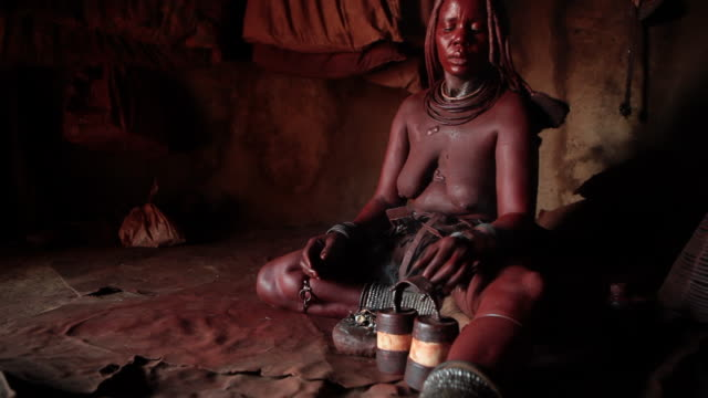 indigenous himba women from namibia doing her cleaning ritual. - indigenous culture stock videos and b-roll footage